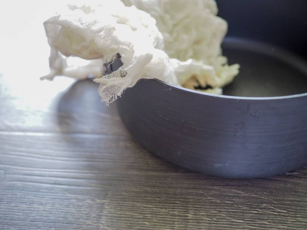 A large shallow saucepan on a gray wooden surface, draped with cheesecloth.