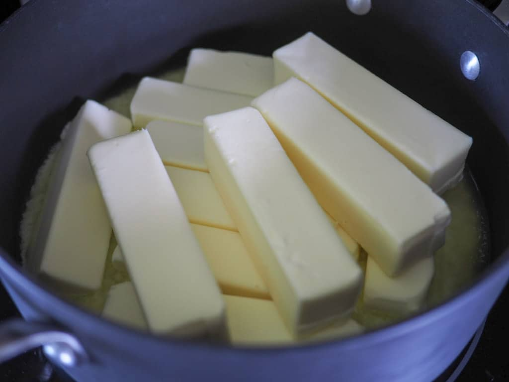 A large black saucepan filled with 12 sticks of butter.