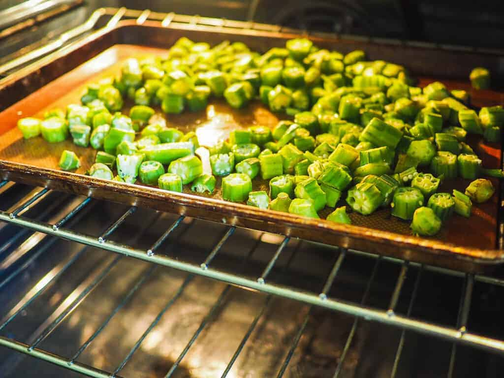 A non-stick baking sheet with cut okra.