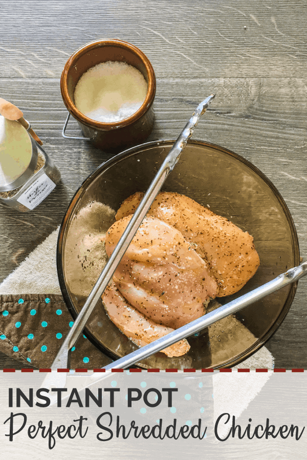 Raw chicken breasts in a brown glass bowl with metal tongs, salt, and herbes de provence on a gray wood floor.