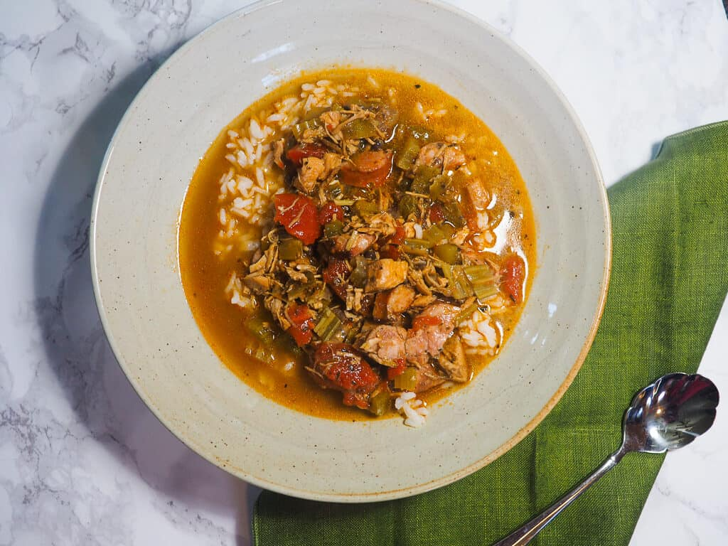 A white bowl of gumbo and a green napkin on a marble countertop.