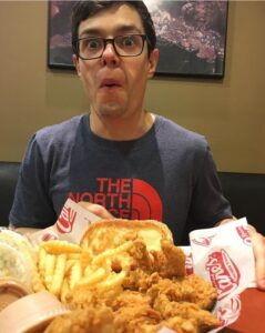 A man with glasses in a blue shirt eating chicken fingers at Raising Cane's.