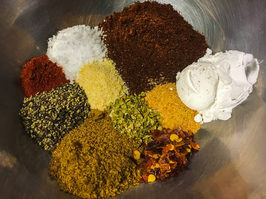 A metal bowl filled with colorful taco seasoning.