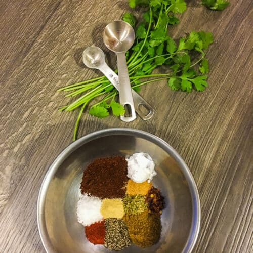 Taco seasoning in a bowl with cilantro and two measuring spoons on a gray wood surface.