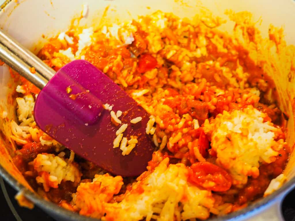 A pot of rice with tomato sauce and a purple spatula.