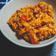 A bowl of creole tomato rice with chicken and sausage with a blue and white napkin.
