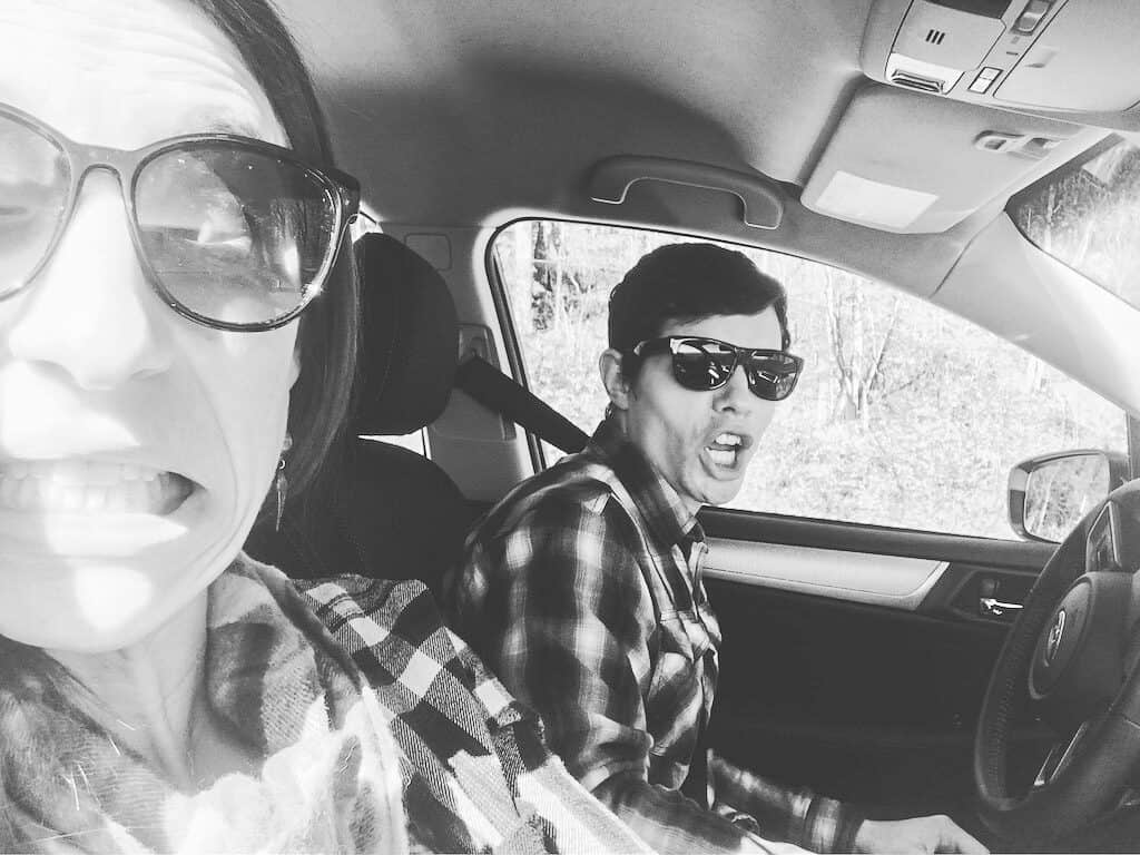 A man and a woman in a car wearing flannel and sunglasses in black and white.