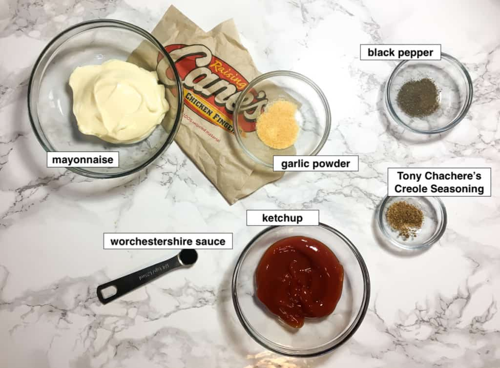 A marble board with the labeled ingredients for making Raising Cane's Sauce - mayonnaise, ketchup, Worchestershire Sauce, black pepper, garlic powder, and Tony Chachere's seasoning.