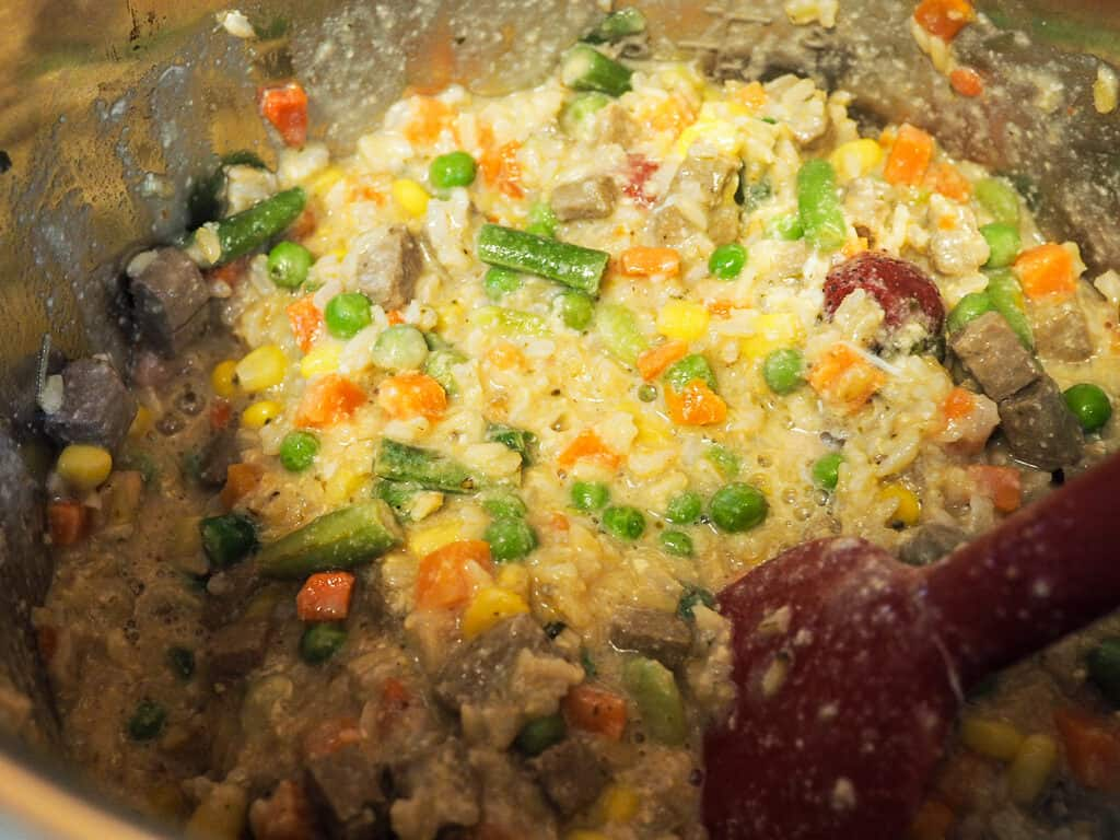 An instant pot with ground beef, vegetables, and rice cooking.