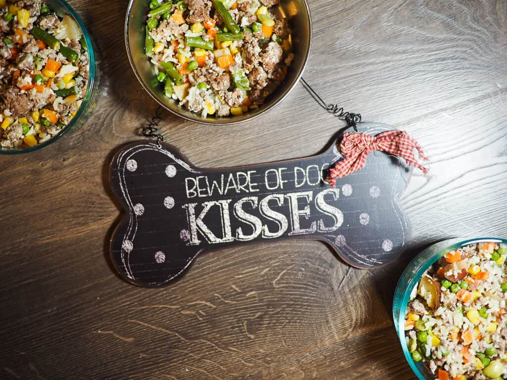 "Bowls of ground beef, vegetables, and rice with a ""Beware of Dog Kisses"" sign on a gray wood background."
