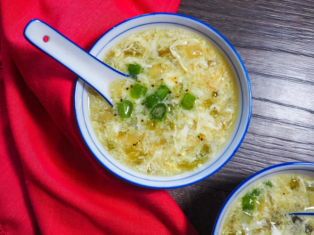 Two small bowls of egg drop soup with a red napkin and ceramic spoon.