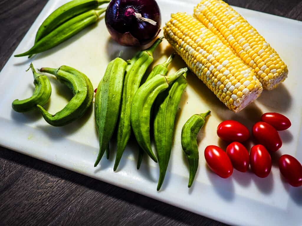 Corn, okra, cherry tomatoes, and a red onion with a white cutting board and knife on a gray background.