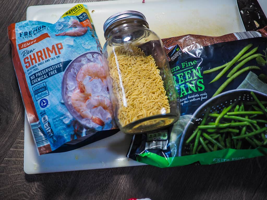 A bag of shrimp, a bag of green beans, and a jar of orzo on a gray background.