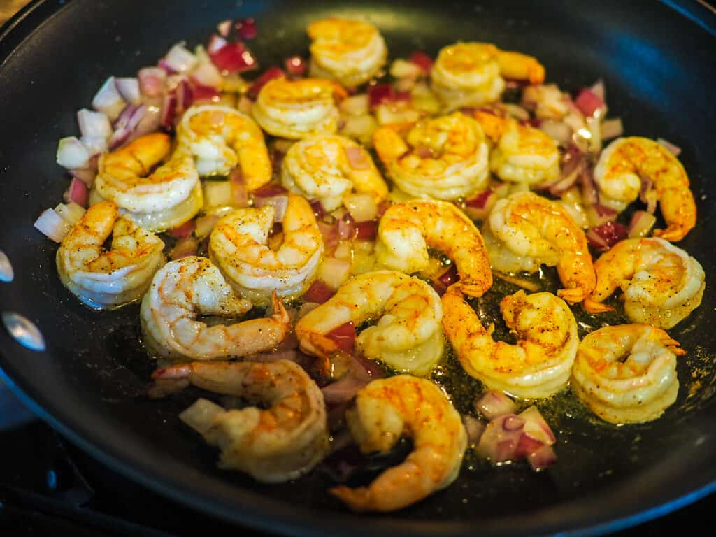 A saute pan with red onion and cooked shrimp in butter with a purple spatula.