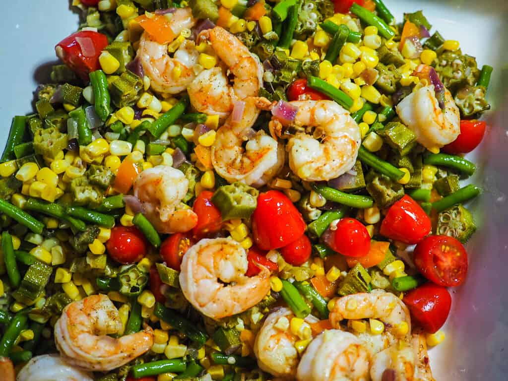 A white casserole dish with shrimp, tomatoes, corn, and okra.