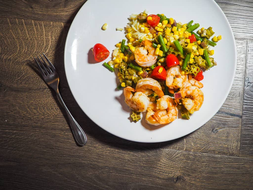 A white dish with shrimp, tomatoes, corn, and okra and a fork on a gray background.