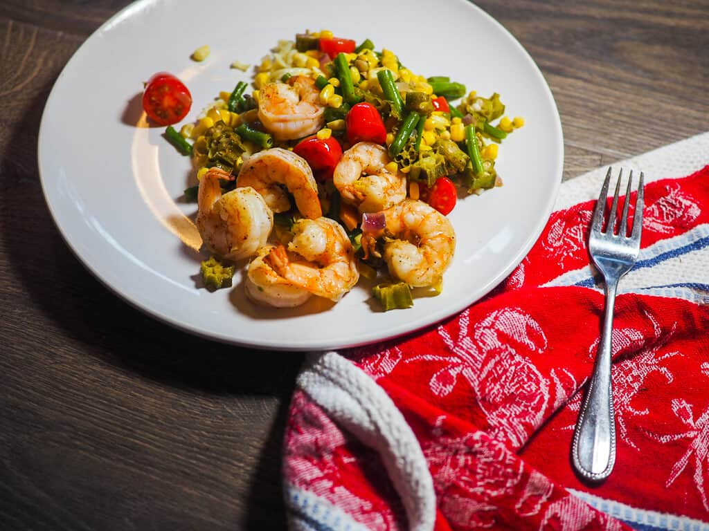 A white dish with shrimp, tomatoes, corn, and okra and a red and white dishtowel with a fork on a gray background.