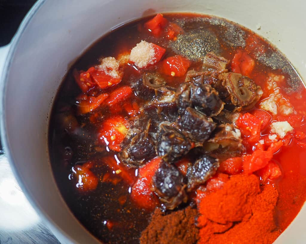 A white pot with tomatoes, dates, spices, and a sauce simmering to make barbecue sauce.