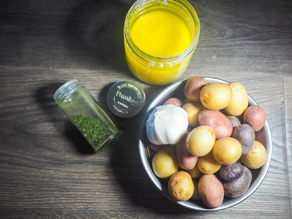 A jar of parsley, a jar of ghee, and a metal bowl of baby potatoes with a head of garlic on a gray wood background.
