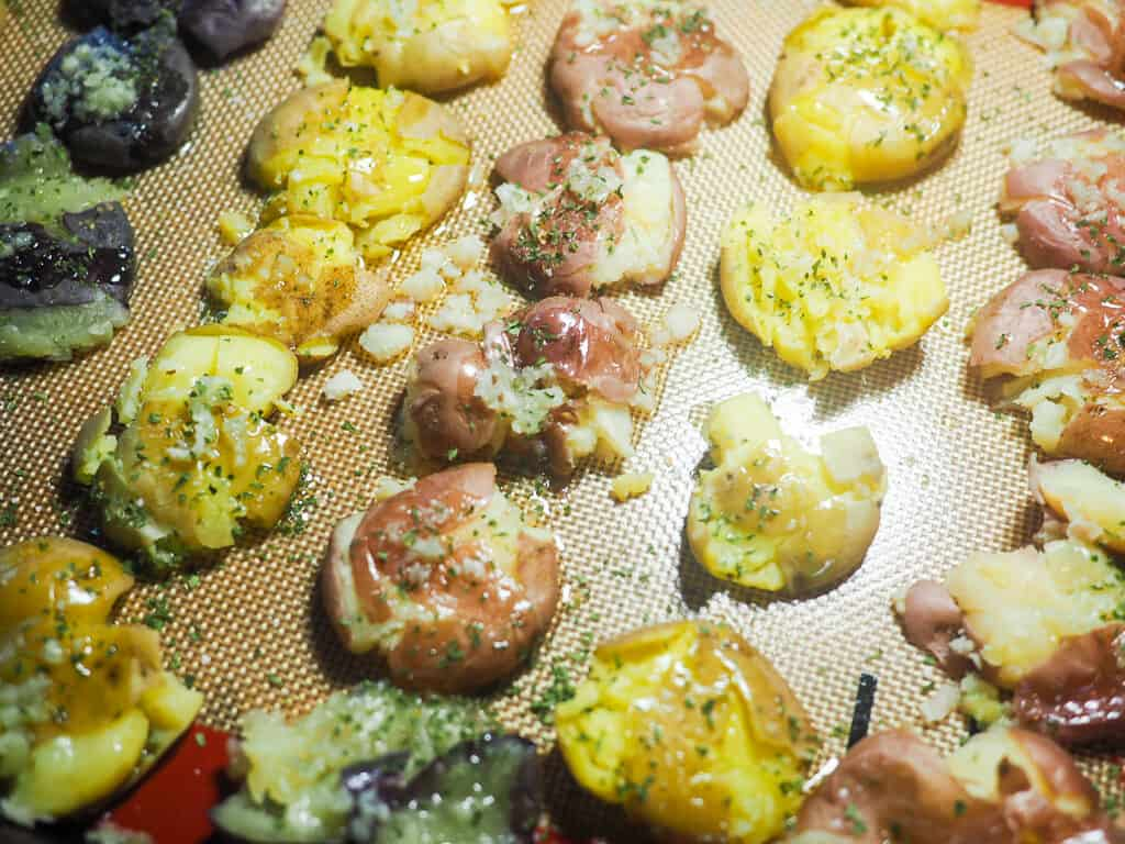 Smashed baby potatoes on a non-stick baking mat with ghee, garlic, and parsley.