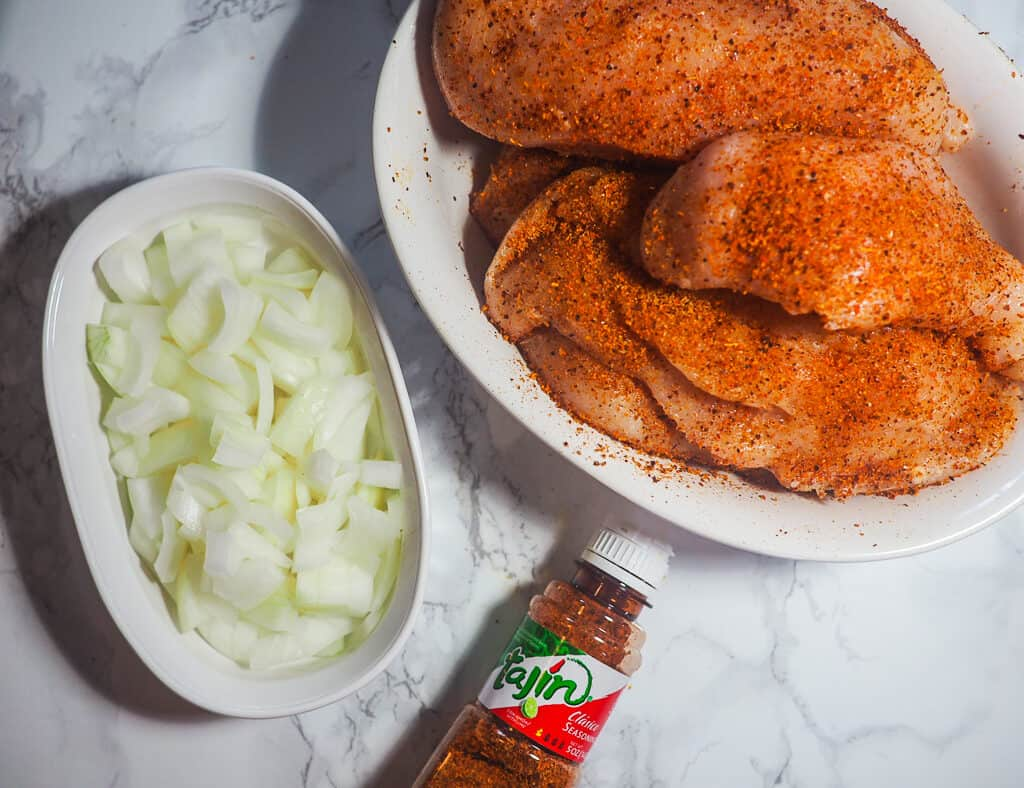 Seasoned chicken in a white bowl, diced onions, and a bottle of Tajin seasoning on a marble countertop.