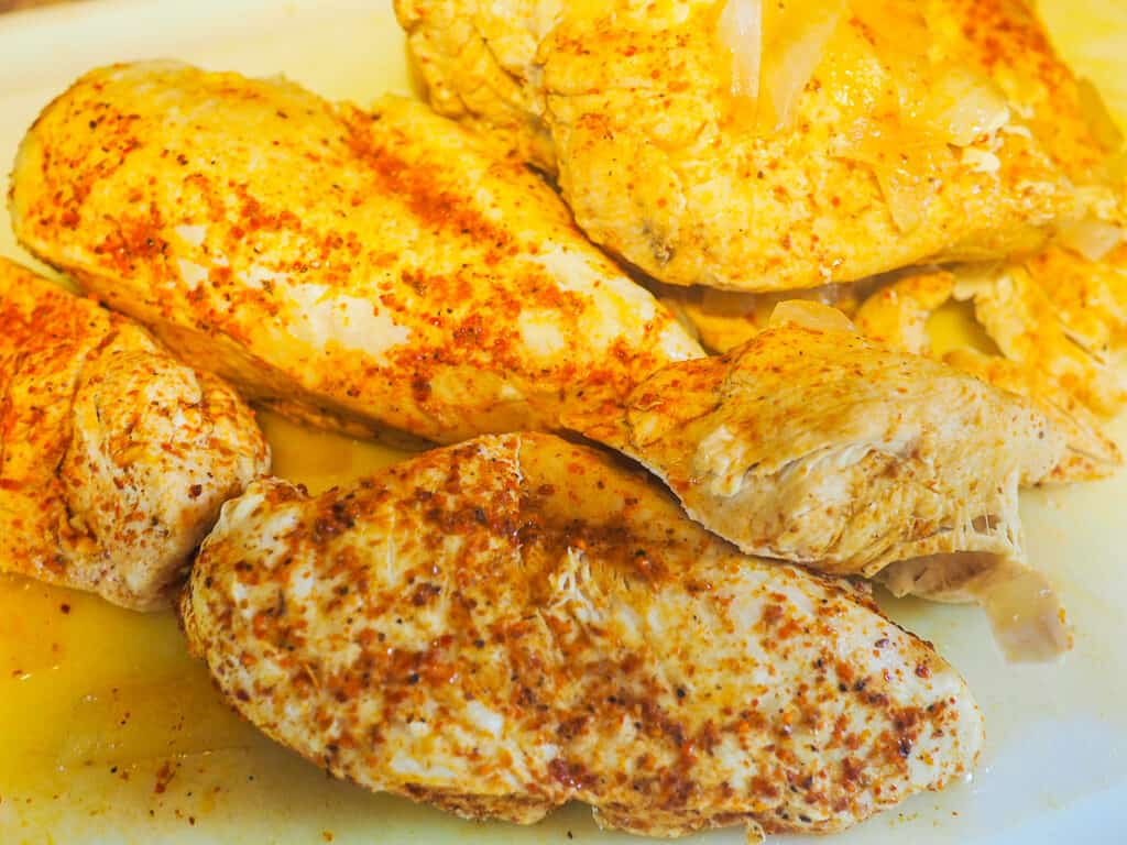 Cooked chicken breast with chili lime seasoning on a white cutting board.