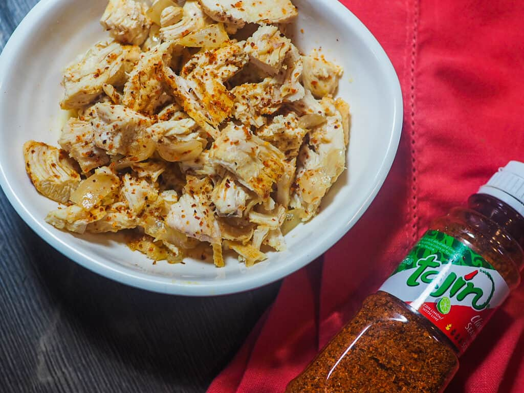 A white bowl of diced chicken and onions with chili lime seasoning with a red cloth napkin and a fork on a gray wooden background with a bottle of Tajin seasoning.