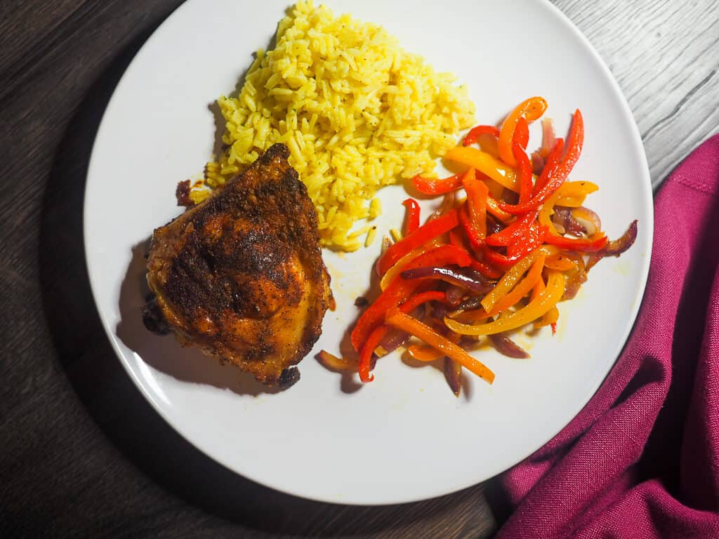 A white plate with a crispy chicken thigh, sautéed bell peppers, and rice pilaf.