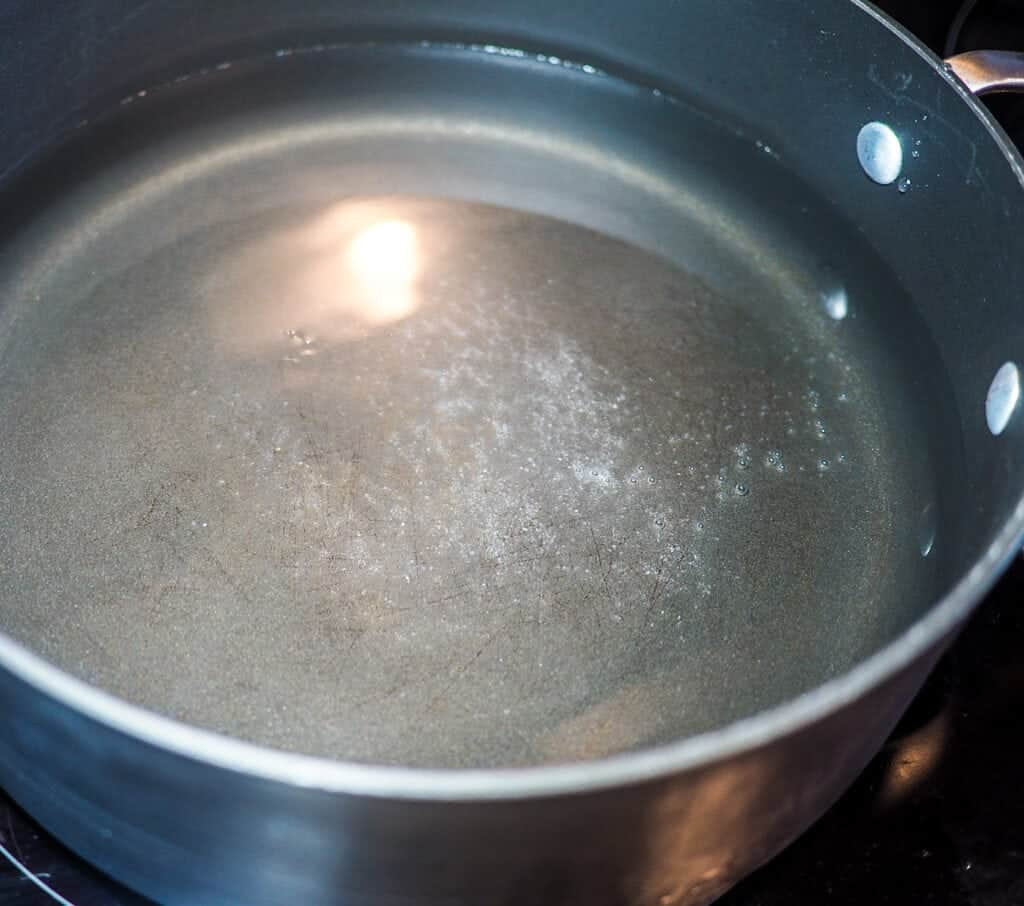 A black pot with water and salt, just beginning to boil.