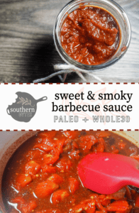 A jar of barbecue sauce with a ribbon around the top on a gray wooden background with a pot of sauce cooking.