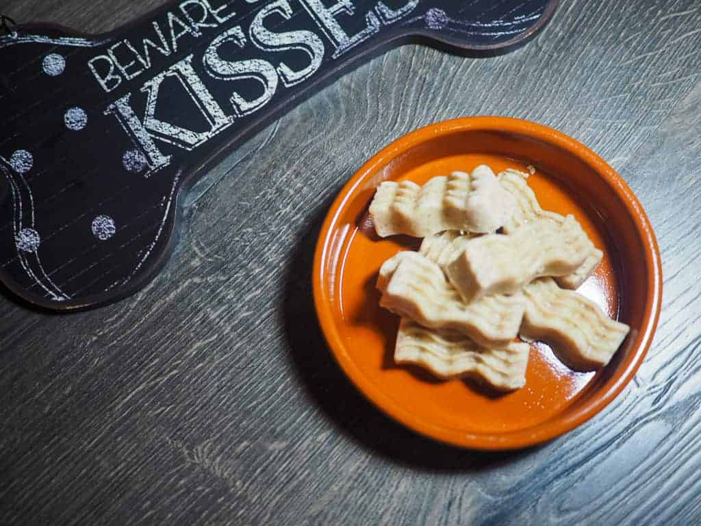 A brown bowl with frozen peanut butter dog treats shaped like bacon and a beware of dog kisses sign.