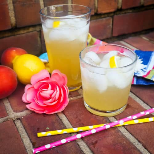 Peach lemonade with ice in a square glass and two peach on a rainbow placemat.