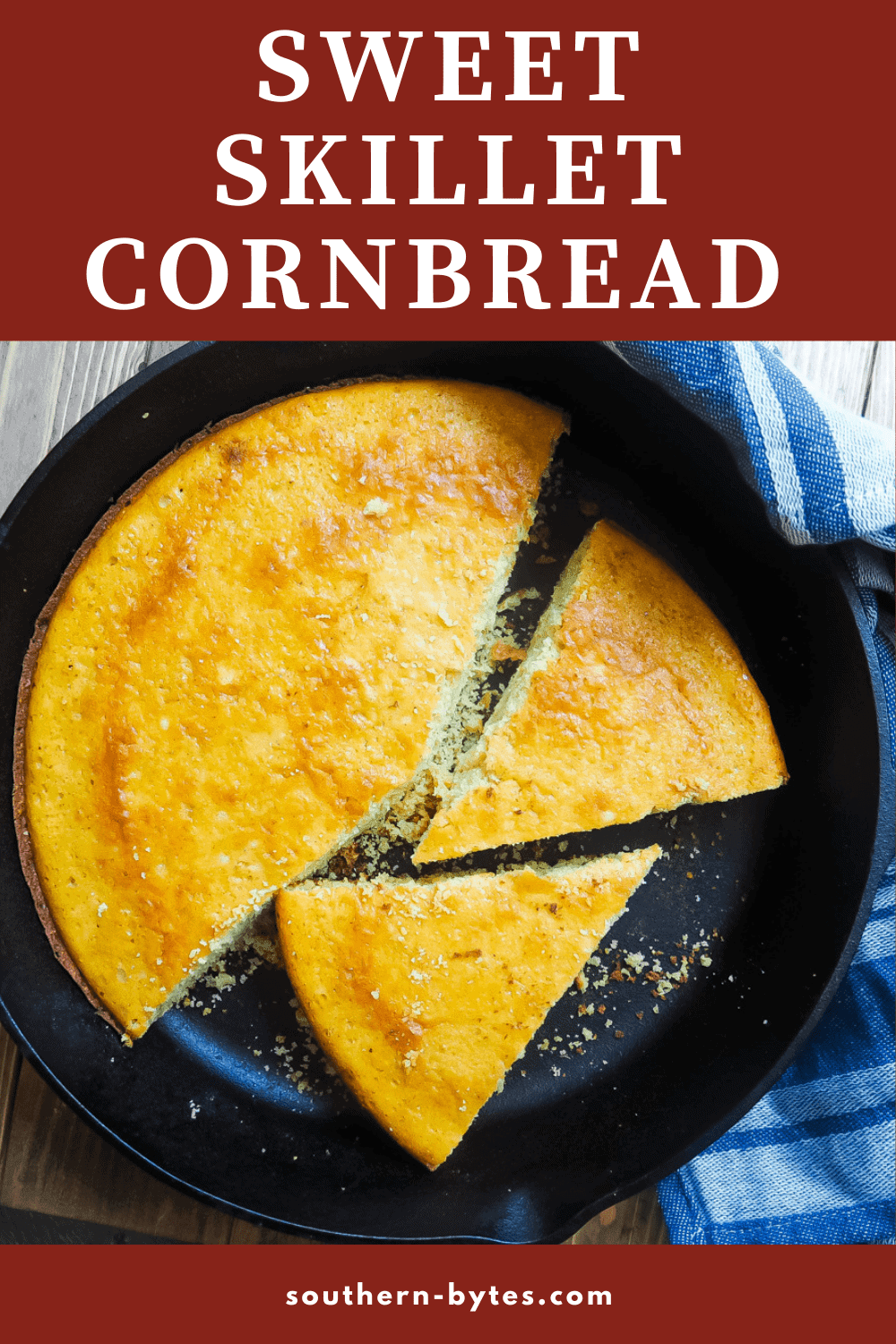 Cornbread in a cast iron skillet with a red and white dish towel on a gray wood background.
