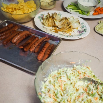 A kitchen counter with hot dogs, coleslaw, a bloomin onion, and dishes of vegetables.