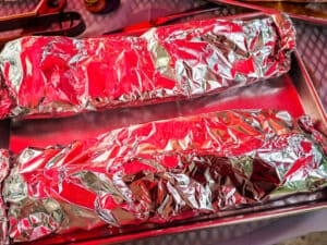 Racks of ribs wrapped in foil on a silver tray.
