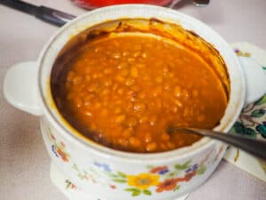A small crock pot filled with baked beans.