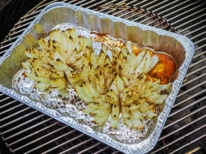 A bloomin onion in an aluminum pan on a grill.