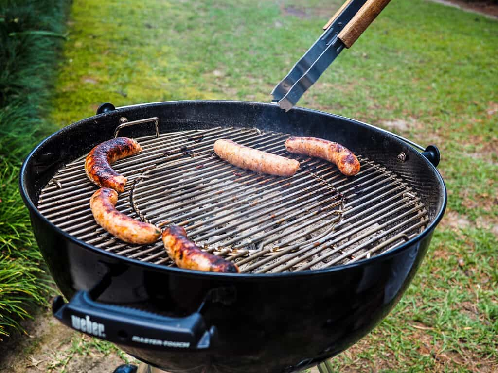 Green onion sausage on a round charcoal grill.