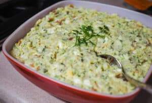 A large red and white bowl with egg and potato salad.