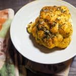 A roasted cauliflower on a white dish with a fall colored napkin.