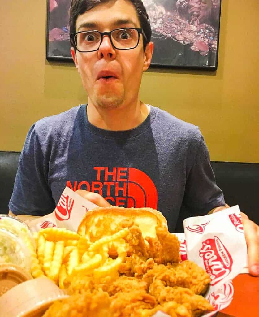 A brown haired man in a blue shirt eating french fries and fried chicken at Raising Canes in New Orleans.