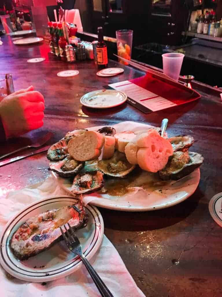 A plate of chargrilled oysters on a bar top in a dark room.