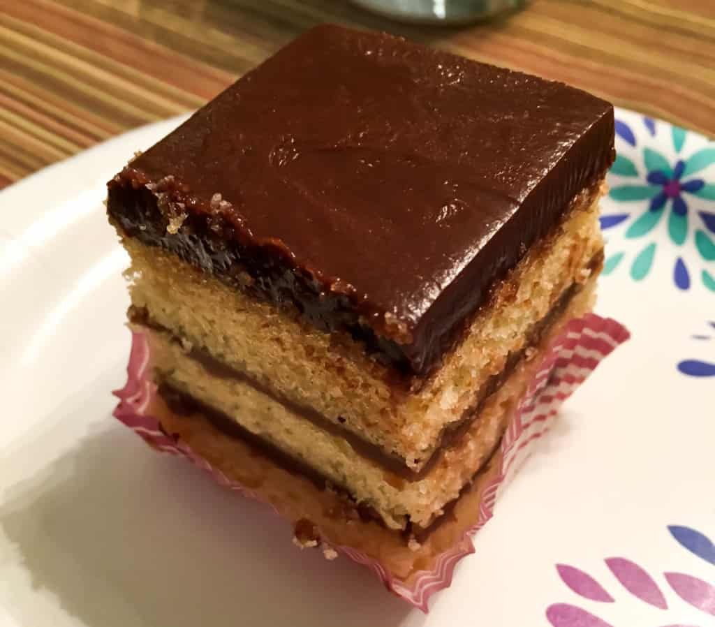 A square of chocolate doberge layer cake on a paper plate.