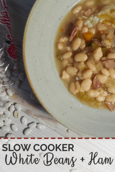 A bowl of white beans and ham soup on a white wooden background with a bag of spilled Camellia Brand White Northern Beans.