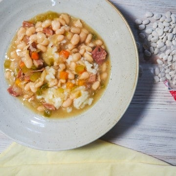 White beans and ham soup in a gray bowl on a white wooden background with a bag of spilled Camellia Brand White Northern Beans with a yellow napkin.