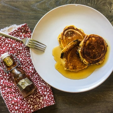 A white plate with three paleo pancakes soaked in maple syrup and a red napkin with a small bottle of maple syrup.