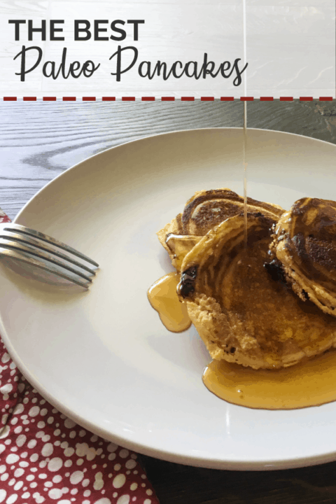 A white plate with three paleo pancakes and a red napkin with a drizzle of maple syrup.