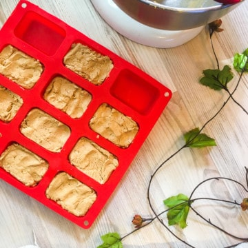 A red silicone loaf baking sheet filled with peanut butter perfect bars and a mixing bowl with a red spatula in it.
