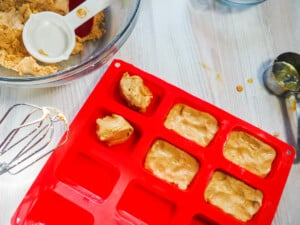 A red silicone loaf baking sheet being filled with peanut butter perfect bars and a mixing bowl with a red spatula and a measuring cup in it.