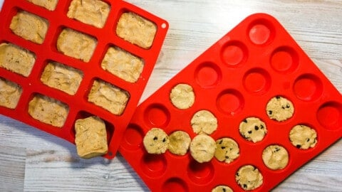 Two red silicon baking mats - one filled with rectangular peanut butter perfect bars and one filled with mini-muffin sized peanut butter perfect bars and peanut butter and chocolate chip perfect bars.